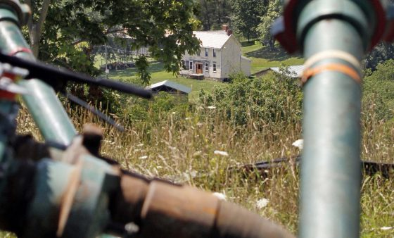 This July 27, 2011 file photo shows a farmhouse in the background framed by pipes connecting pumps where the hydraulic fracturing process in the Marcellus Shale layer to release natural gas was underway at a Range Resources site in Claysville, Pa.